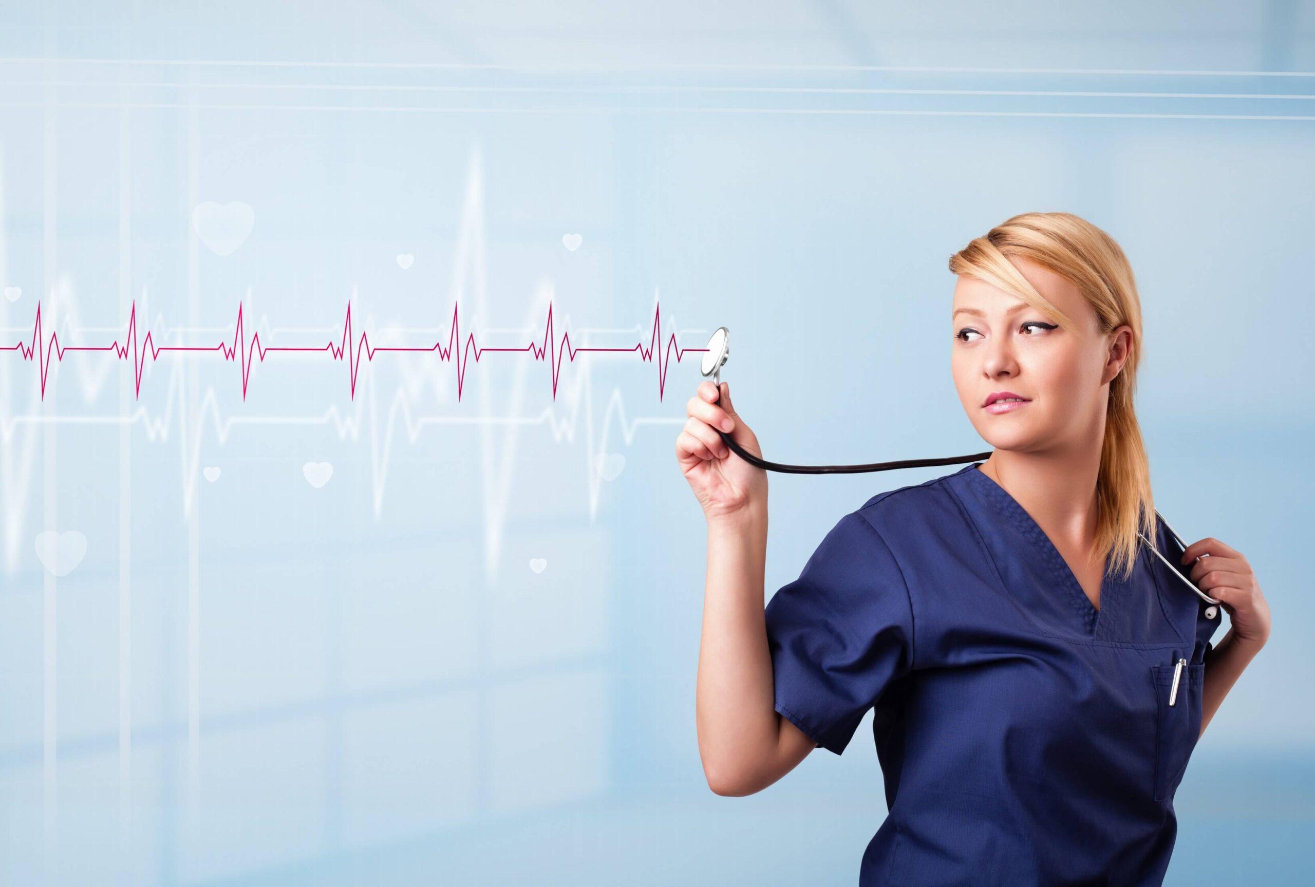 lekarka o jasnych włosach trzyma stetoskop, w tyle widoczna linia izoelektryczna
