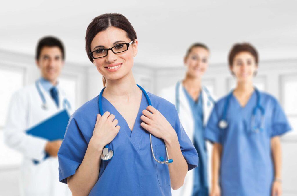 zespół doświadczonych lekarzy, na pierwszym planie młoda uśmiechnięta lekarka