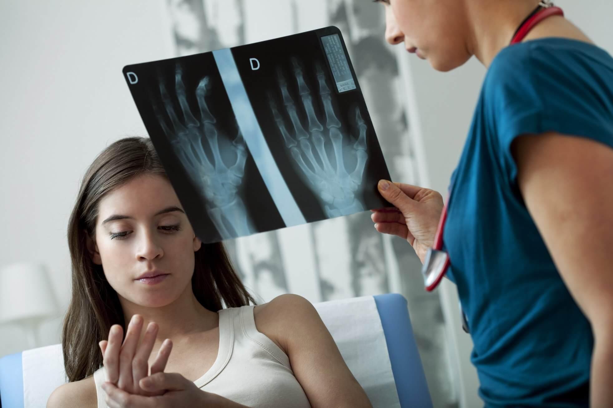 młoda dziewczyna z zespołem cieśni nadgarstka leży na kozetce podczas wizyty lekarskiej