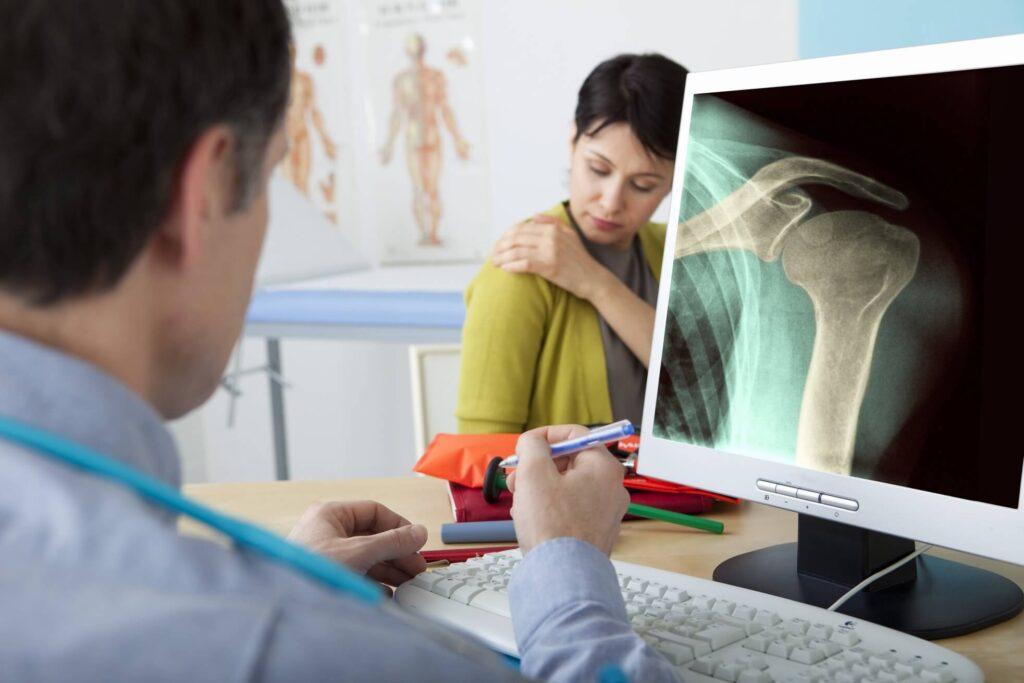 kobieta z bólem barku w trakcie badania lekarskiego, lekarz siedzący za biurkiem ogląda zdjęcie RTG stawu