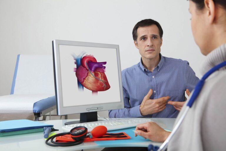 mężczyzna skarżący się na ból w klatce piersiowej, lekarz kardiolog za biurkiem spogląda na wizualizację serca znajdującą się na monitorze