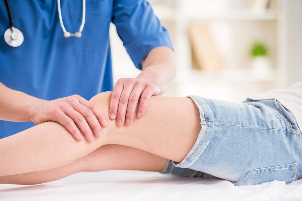 lekarz ortopeda w trakcie badania stawu kolanowego