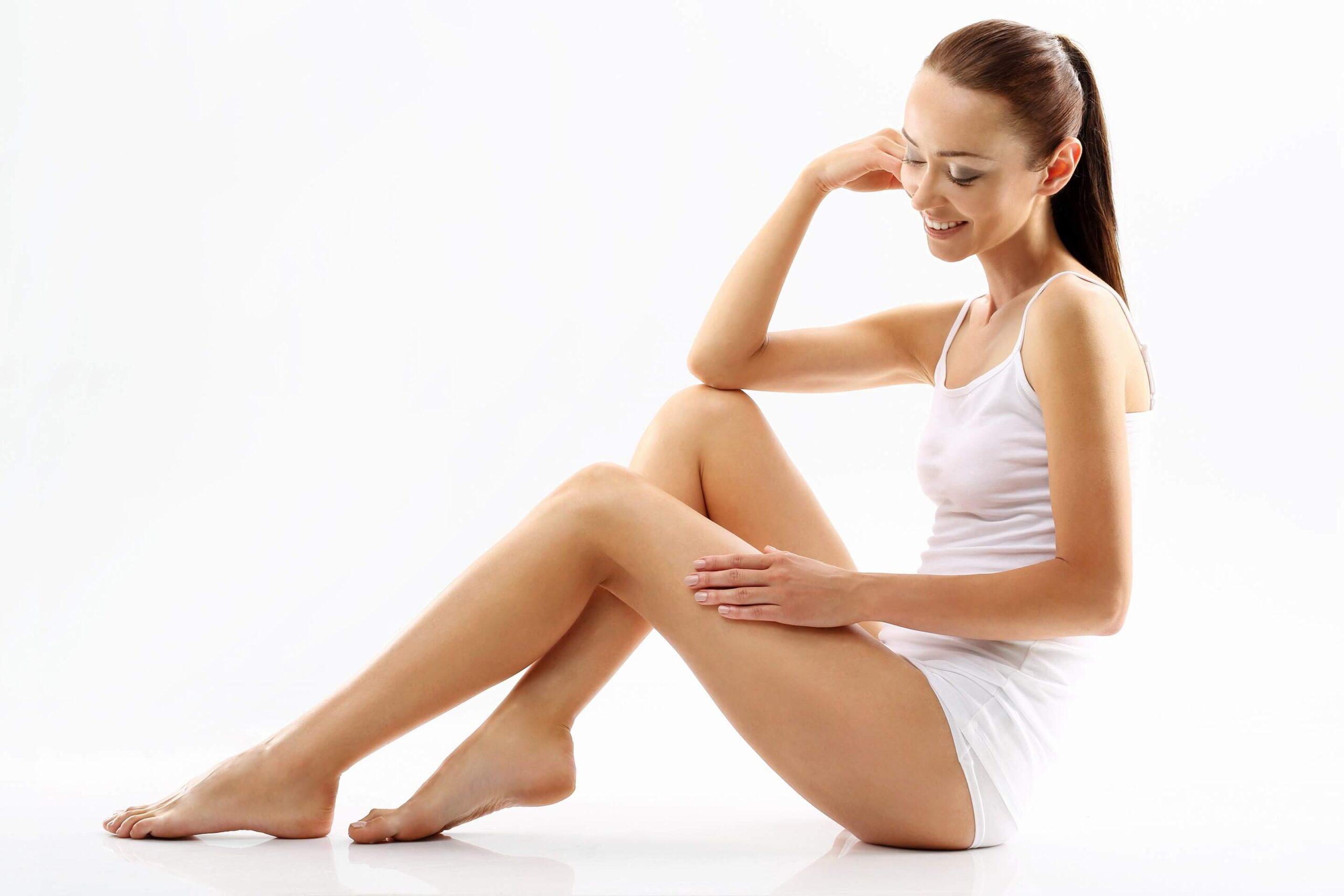 młoda, piękna kobieta prezentuje swoje zgrabne i zdrowe nogi bez żylaków i znamion