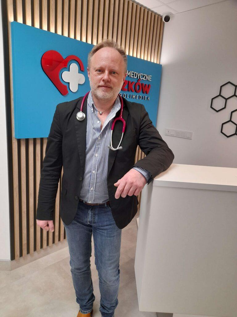 dr Marcin Rzeszutko stoi oparty o ladę rejestracji centrum medycznego Myszków